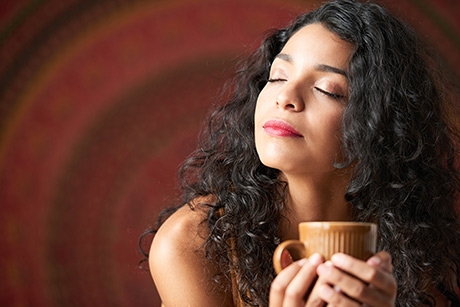 dark haired woman holding a cup of coffee with eyes closed