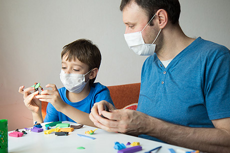 father and son in masks playing with modeling clay